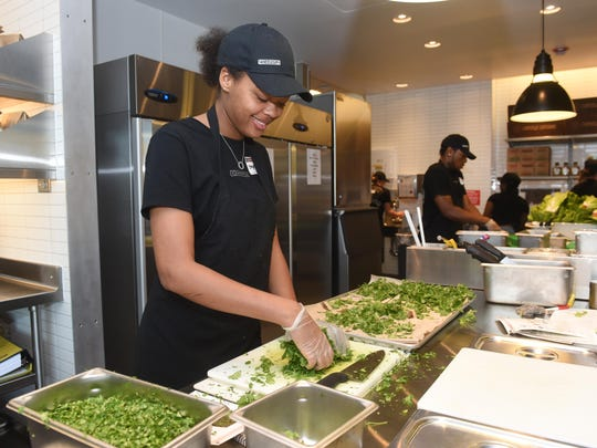 Stephanie Hicks chops cilantro at Chipotle, which opened at Ford Road and Lilley Road. The restaurant near Interstate 275 and IKEA is filled with a high volume of people — good for business, bad for traffic.