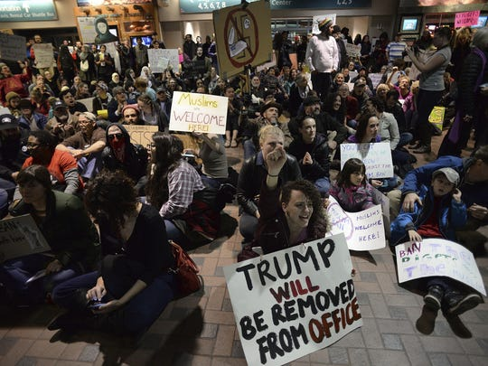 Jacklyn Parsons, center, raises her fist in the air Sunday while participating in a sit-in protest at the Albuquerque Sunport. A group of 1,000 protesters took over the arrival and departure area to express their opposition to President Trump's executive order banning entry to the U.S to citizens from seven predominantly Muslim countries.
