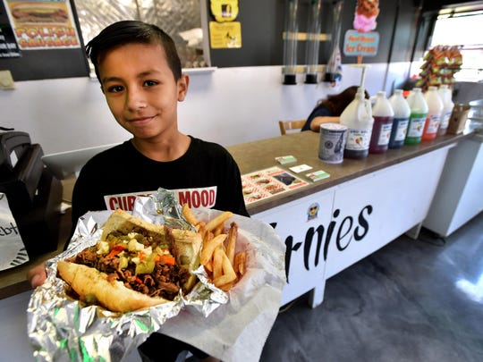Abraham Villegas brings a Chicago-style Italian beef sandwich to a customer in his father's restaurant Ernies in Covert.