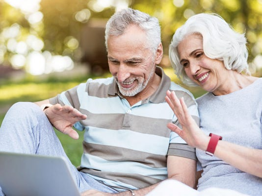 Elderly family using internet for communication sitting in a park