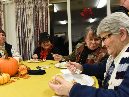 Irene Bowman of Winooski, from left, dines with friends, including Nan Spence of Winooski, Gillian Wiatt of Winooski and Sister Germaine Richer of Winooski, at the Community Harvest Dinner at the O'Brien Center on Tuesday.