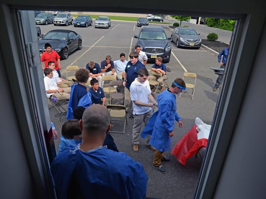 St. Augustine Prep students wait their turn to go inside the trailer, which is sent by its owner to hospitals and medical offices around the country.