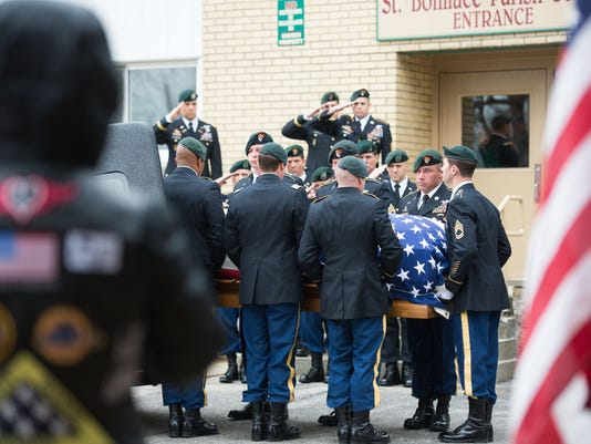 Patriot Guard Riders salute the body of Bay City soldier Sgt. 1st Class Michael Cathcart after funeral service Nov. 26