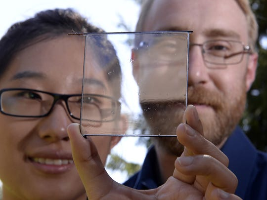 Michigan State University professor of chemical engineering and materials science Richard Lunt and graduate student Yimu Zhao show a transparent luminescent solar concentrator module developed in Lunt's MSU lab in East Lansing.