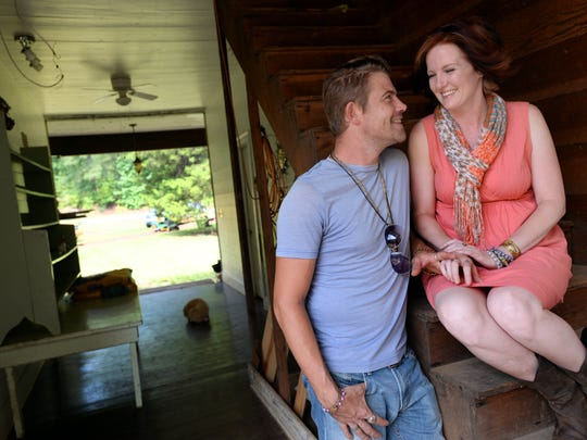 Chris Parker and Jackie Lewis sit in the breezeway of the 1888 two-story dogtrot home they are renovating in rural Claiborne Parish.