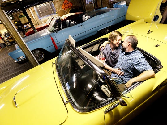 Erin and Alan Berry sit in one of their vintage cars in their building on Southern.