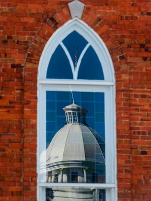 The state capitol building reflected in a window of Dexter Avenue King Memorial Baptist Church in Montgomery, Ala., on Friday January 13, 2017.