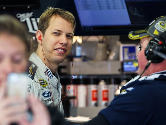 Driver Brad Keselowski smiles while talking to a member of his crew during practice for the Sunday's NASCAR Sprint Cup series auto race at New Hampshire Motor Speedway in Loudon, N.H., Friday, Sept. 25, 2015  (AP Photo/Cheryl Senter)