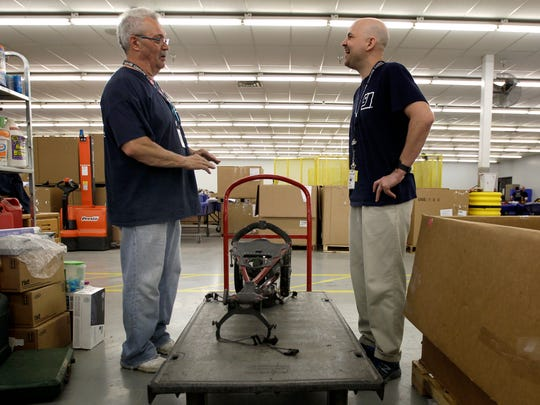 Goodwill Outlet Center production and sales floor leader Jebb Filz, right, talks with Norm Parrotte about a piece of donated equipment in Appleton. Seven years after being released from prison, Filz has earned a marketing degree and bought a house.