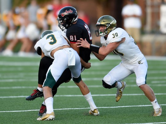 Catholics Jack Jancek (3) and Cody Duncan (30) take down Maryville's Blake Watson (81) during a high school football game at Maryville High School against Knoxville Catholic High School Friday, Aug. 18, 2017.