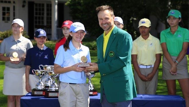 Madilyn Newman receives her trophy for the Girls 12-13 best putt from Masters champion Trevor Immelman of South Africa during the Drive, Chip and Putt National Finals at Augusta National Golf Club on Sunday, April 2, 2017.