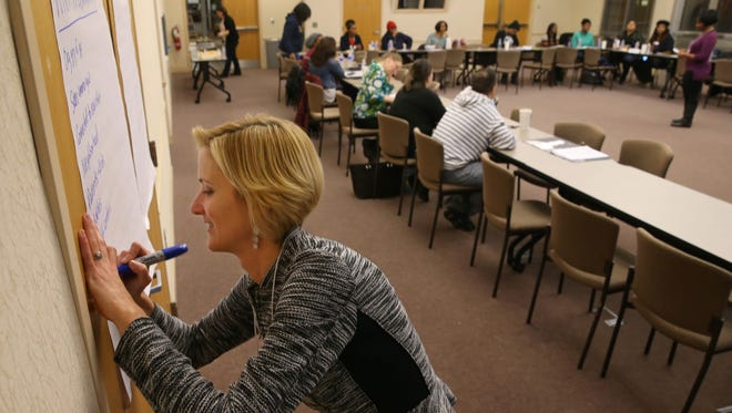 """Mary Staropoli, Rochester, lists examples given by the class on 'What is Community?"""" at the Parent Leadership Training Initiative class held in downtown Rochester Monday, Dec. 5, 2016."""
