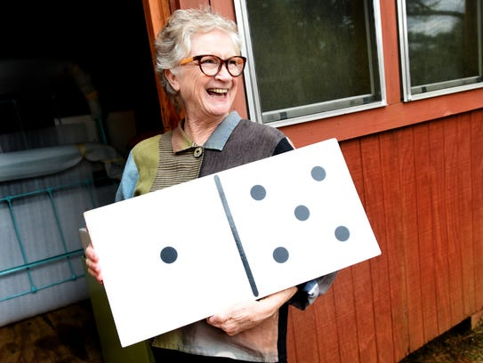 Wanda Anglin holds up a large domino that she plans