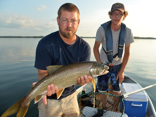 Nick Hutchinson, foreground, and Hobby Jackson admire a lake trout before releasing it.