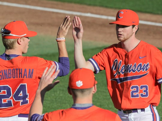 Clemson junior pitcher Charlie Barnes (23) is greeted after getting out of the the top of the first inning on Friday at Doug Kingsmore Stadium in Clemson.