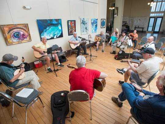 A group of musicians perform during the Panhandle Folk Music Club meeting at the Artel Gallery in Pensacola on Wednesday, April 5, 2017.