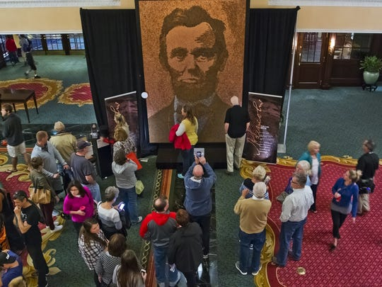 "Crowds look at Richard Schlatter's ArtPrize entry ""A. Lincoln""  in Grand Rapids on Friday, Oct. 6, 2017.  The entry, which was a 2-D finalist, won the $200,000 Public Vote Grand Prize. Each year of Lincoln pennies, from 1909 through 2017, is represented in the piece. It includes 1,681 steel pennies from 1943, which form Lincoln's shirt."