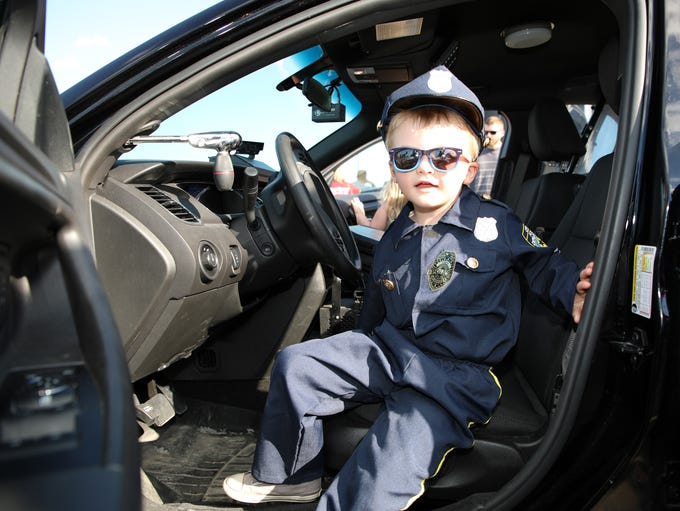 Ryan Fain, 4, of Ankeny checks out the squad car during