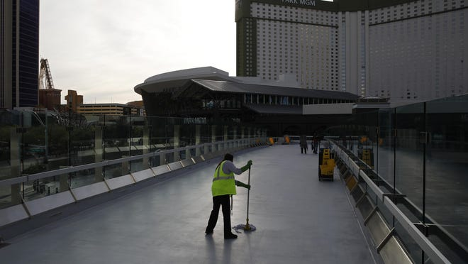 FILE - In this March 31, 2020, file photo, a worker cleans along the Las Vegas Strip devoid of the usual crowds as casinos and other business are shuttered due to the coronavirus outbreak in Las Vegas. Nearly 245,000 people have filed for unemployment in Nevada since casinos and other businesses closed in mid-March to keep people from congregating and spreading the new coronavirus, according to U.S, Department of Labor figures posted Thursday, April 9. (AP Photo/John Locher, File)