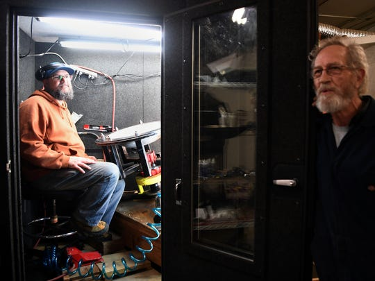 Chet Plant sits in a sound proof room where he uses a pneumatic hammer to forge Saraz Handpans April 17, 2018, as Steve Garner leans on the door.