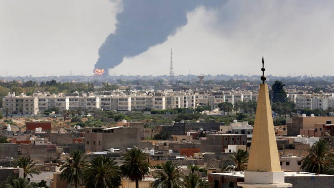 Black smoke billows from an airport oil depot struck as warring militias battled  for control of Libya's Tripoli airfield in July 2012.