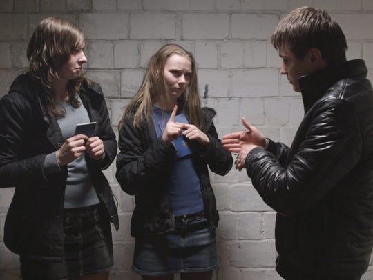 Anya (Yana Novikova), center, and two friends sign
