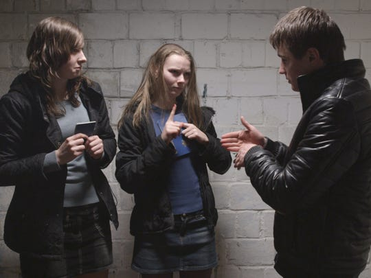 """Anya (Yana Novikova), center, and two friends sign heatedly in Drafthouse Films' """"The Tribe."""""""