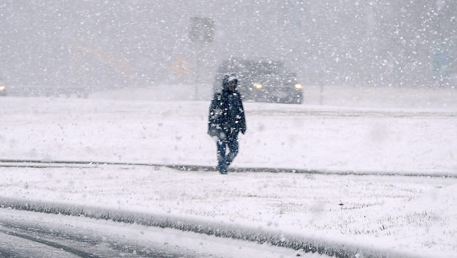 A pedestrian walks during heavy snowfall along Garland Groh Boulevard in Hagerstown, Md., on Tuesday, March 20, 2018.