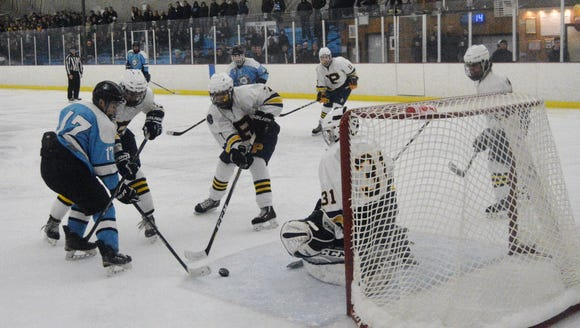 Suffern forward Evan  Cama (17) battles for a puck