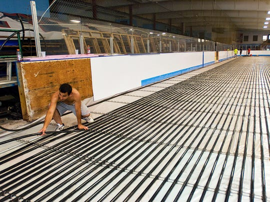 Sean Then stretches piling in a grid across the floor of one of two hockey rinks at the Lakeshore Hockey Arena in Greece in 2011. The work was part of a $250,000 project.