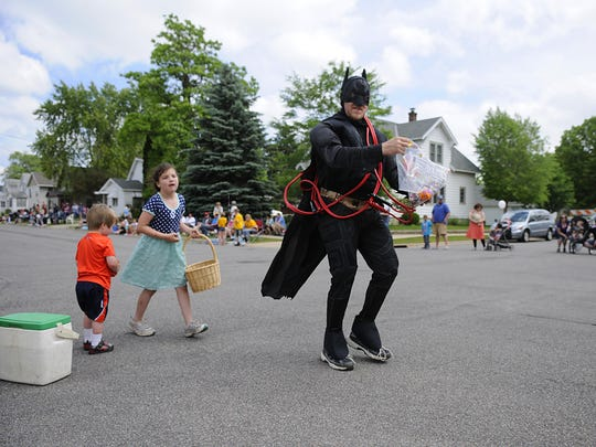 Batman passes out candy to paradegoers during the Family Fun Fest Superhero Grand Day Parade on Saturday in Waite Park.