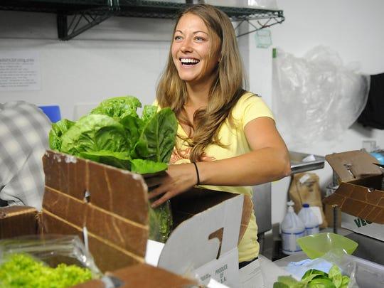 Produce farmer Lisa Baker delivers lettuce to Minnesota Street Market Co-op from her farm, Bakers' Acres, on June 17, 2015.
