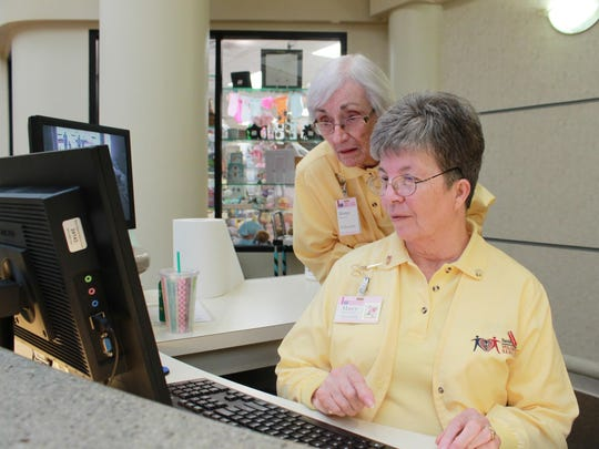 Marcy Bowers, front, and Marge Ryan work a Thursday afternoon at the information desk located at the main entrance of Baxter Regional Medical Center. The two volunteer every Thursday for approximately four hours a week at the hospital.