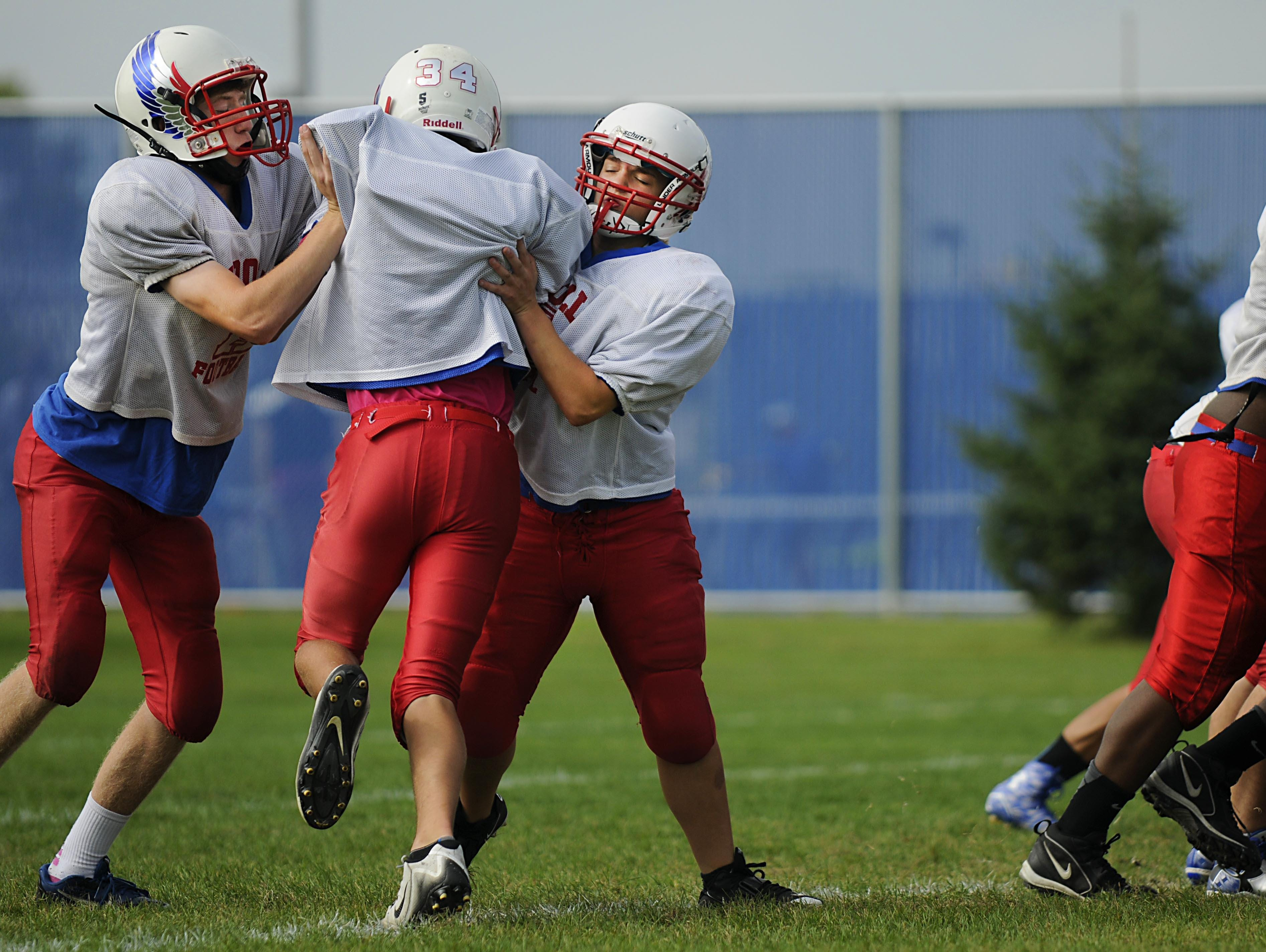 Tight end receiver Jake Reber and linebacker Angie Stolt block wide receiver Peyton Joos at practice on Wednesday at Apollo High School.