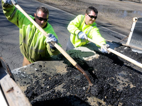File: Vineland Public Works employees Albert Alvarado (left) and Kyle Suprun shovel stones from the back of their truck to fill in potholes on Chestnut Avenue east of Lincoln Avenue in Vineland. March 1, 2010.