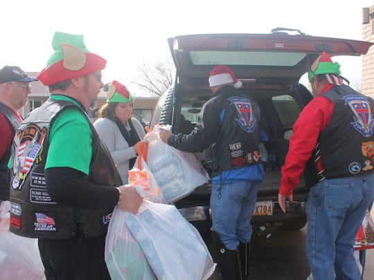 Members of the local chapter of Road Riders for Jesus gather bags full of presents to take inside of the Betty Dare Good Samaritan Center on Saturday.