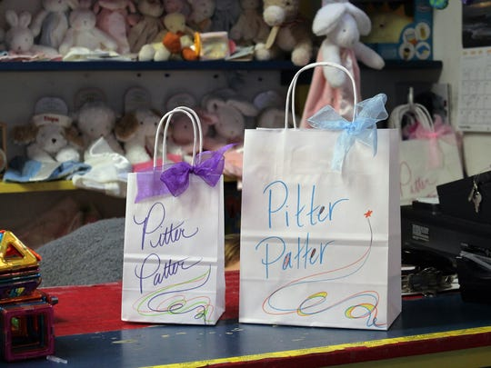 Pitter Patter prides itself on making the shopping experience personal. Everyday, store workers decorate plain white bags with the store's logo, ribbon and tissue paper. It is a personal touch that sets the store a part from chains.