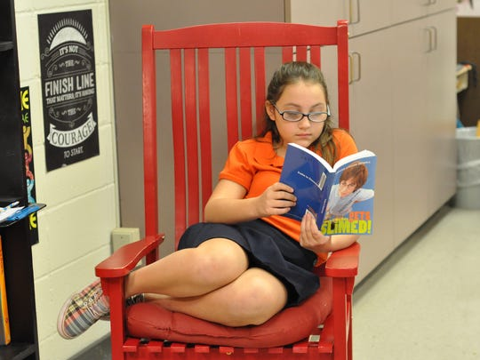 J.B. Nachman fifth-grader Isabella Aguillard reads in a rocking chair in Tammy Dean's classroom.