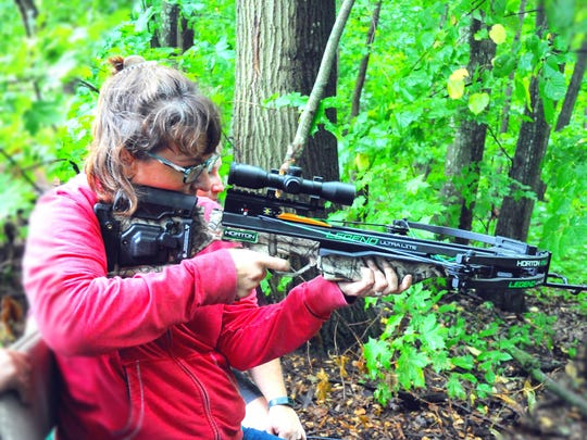 A participant prepares to shoot a crossbow at the 19th
