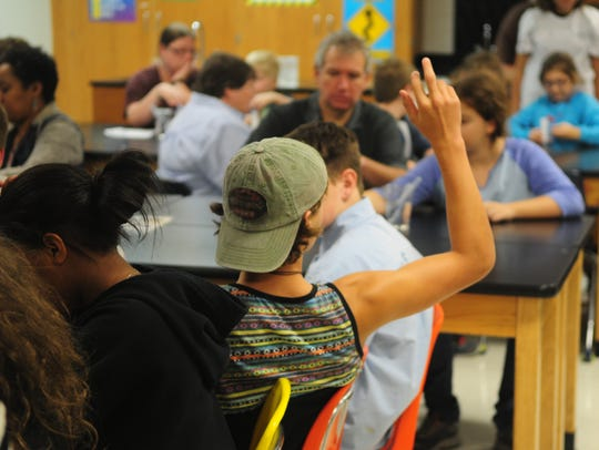 A student raises his hand to ask a question while making