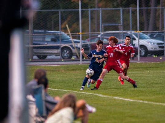 Huskies' Grant Robertson and Big Reds' Connor Stefanski battle for possession Monday, Oct. 17, during boys district soccer action at Port Huron Northern.