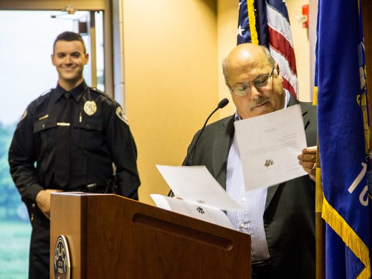 "Franklin mayor Steve Olson ""swears in"" the Franklin Police Department's new K9s: Harley, Rex, and Vito. Background: Officer Kevin Page."