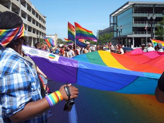 Participants in the Michigan Pride Parade march to