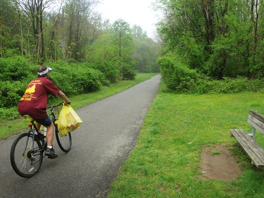A biker rides along Ramsey Bikeway, an asphalt hiking and biking path several miles long, runs along the route of the old NJRT trolley line (1911 to 1928). It's one of 50 NJ rail trails created from the old right-of-ways of disused railroad lines.