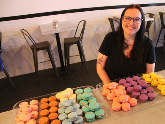 Kat Andreas poses with dozens of macarons she baked