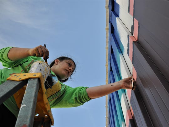 Junior Carley Russell, 17, from Grand Prairie Fine Arts Academy measures a line on a new mural on 301 Locust St. on March 24..