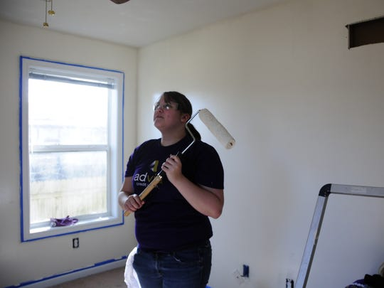Volunteer Ashley Eagle sizes up an interior wall to be painted at a Habitat for Humanity project home in Port Huron on Saturday, April 7, 2018.