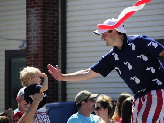 A stilt walker exchanges a very high five with a spectator at the Independence Day Parade in Lexington on Saturday, July 7, 2018.