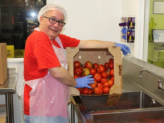 Geoff Lieberman, Macy's Jensen Beach vice president store manager, volunteers in the Elisabeth Lahti Nutrition Center prepping hundreds of pounds of fresh tomatoes for distribution to thousands of Martin County residents.