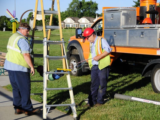 Mike Fritz, left, and Bob Hall work on the lighting Wednesday, July 18, 2018 along the Thomas Edison Parkway in Port Huron.